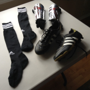 Boy's soccer shoes, chin pads, socks, and ball