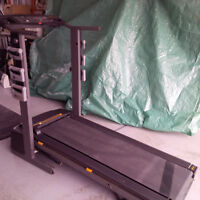 Combination electronic treadmill and weight bench.