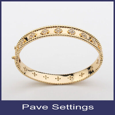 oval bangle with small cubic four leaf clover bracelet in gold