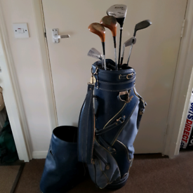 Old Petron golf bag with six odd clubs woods and irons