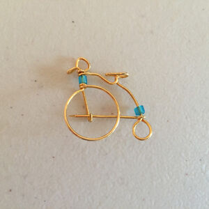 Gold coloured bike brooch with blue beads