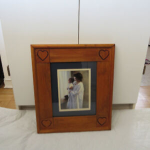 a picture in a wood frame of a mother holding her baby