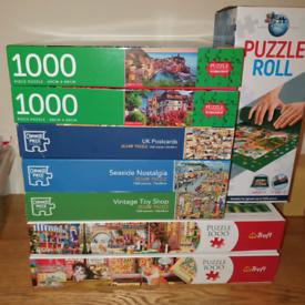 7 x 1000 piece jigsaws, as new, also puzzle mat