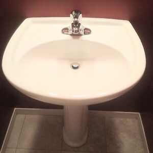white pedestal sink and faucet