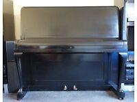 Small black upright piano for sale.