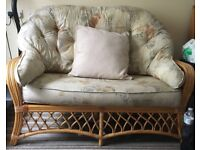 2 seater wicker frame couch with plush cushions