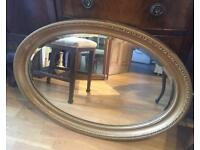 Oval gold ornate Beveled mirror.