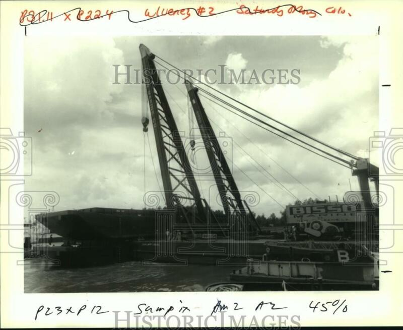 1993 Press Photo A barge suspended on a cable by a crane while another is placed