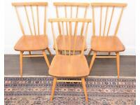 Four Ercol mid-century blonde stick back chairs