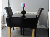 DINING TABLE. (EXTENDING) IN BLACK SHEEN WITH LIGHTWOOD LEGS.