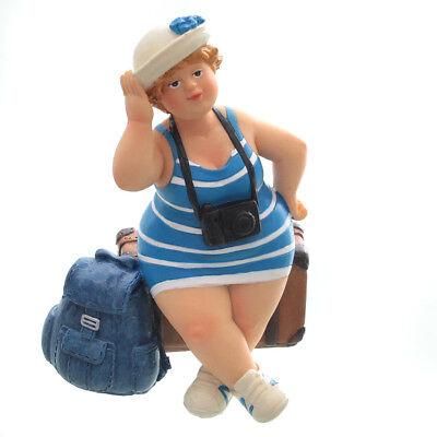 Touristin, sitzend, blau / weiß, mit Koffer und Rucksack