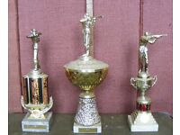 Ten assorted unengraved clay pigeon shooting trophies-12 to 22 inches high.