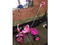 Little girls push along trike