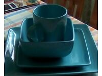 Crockery set of turquoise square plates, bowls and mugs. Fifteen items in total.