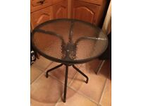 Glass topped round garden table