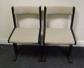 pair of wood and fabric padded chairs.