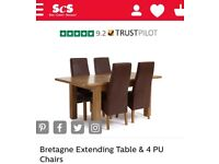 Lovely oak extending dining table with 4 dark brown chairs .