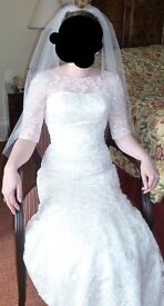 White lace wedding dress, with sleeves and train. Approx size 10. Storage box and veil included.