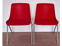 Two red stackable plastic chairs