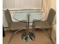 Glass dinning table. 4 faux leather chairs.