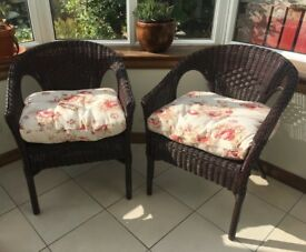 2 wicker chairs with matching floral cushions