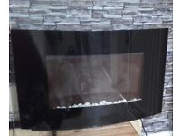 Electric fire Two heat settings. Remote control. Lights up. Black with glass front an white stones