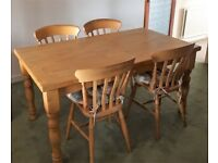 Farmhouse table and four Carver Chairs.