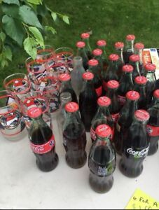 8 Coca Cola glasses and 25 bottles