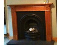 Cast iron gas fireplace with wood surround and gas fire coals