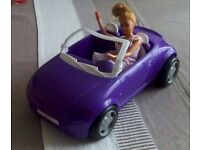 Purple barbies convertible car with a barbie figure, included is a bag of various clothes.