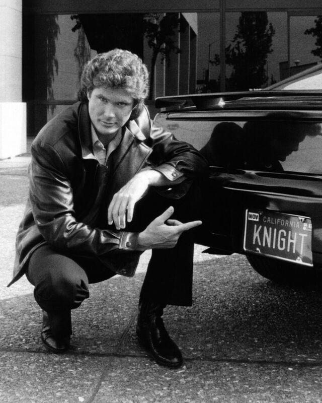 KNIGHT RIDER DAVID HASSELHOFF POINTS TO KNIGHT LICENSE PLATE ON KITT 8X10 PHOTO