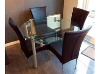 Extending clear glass dining table & 4 padded black PVC chairs.