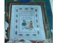 New counted cross stitch kit of a sampler. Picture is of children, with alphabet, flower border.