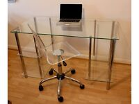 Clear glass and chrome desk and clear acrylic office chair.
