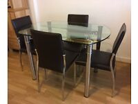 PRICE REDUCED. Modern extendable glass table with 4 chairs. 76cm x 115cm (115cm round extended)
