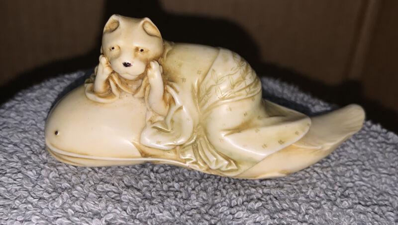 Japanese Figurine Tanuki Raccoon Lying On Catfish