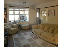 Four seater pillow back sofa, two armchairs and a footstool
