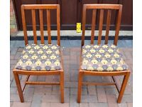 A pair of solid wood framed dining pairs