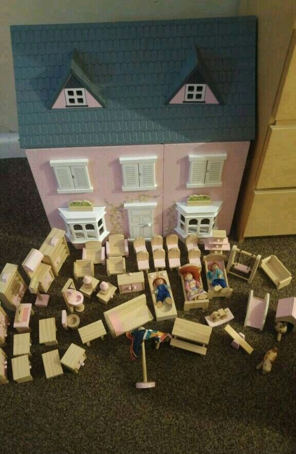 Wooden dolls house with lots of furniture and dolls