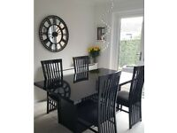 Extendable black dining table with 6 chairs