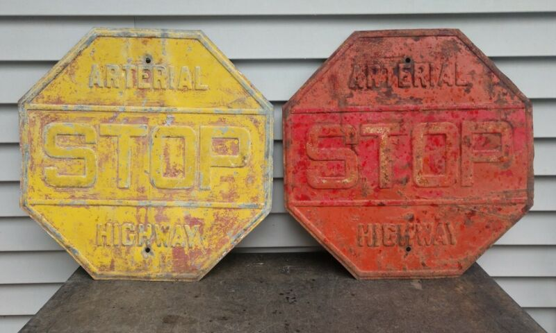 Two antique arterial highway stop signs 1 red 1 yellow