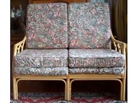 Two seater settee with cane frame and six cushions. Good condition.