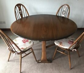 Ercol round drop-leaf dining table and four chairs plus carver, dark wood, good condition.