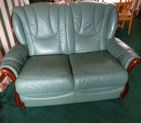 Green leather couch with wood accents