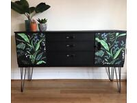 Black sideboard with leaf print design on doors and hair pin legs