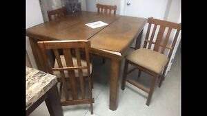New pub height oak dining table with four matching stools $800.