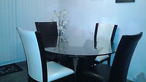 Glass dining room table and leather chairs