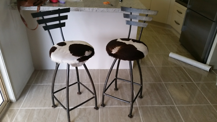 Two iron and cow hide bar stools