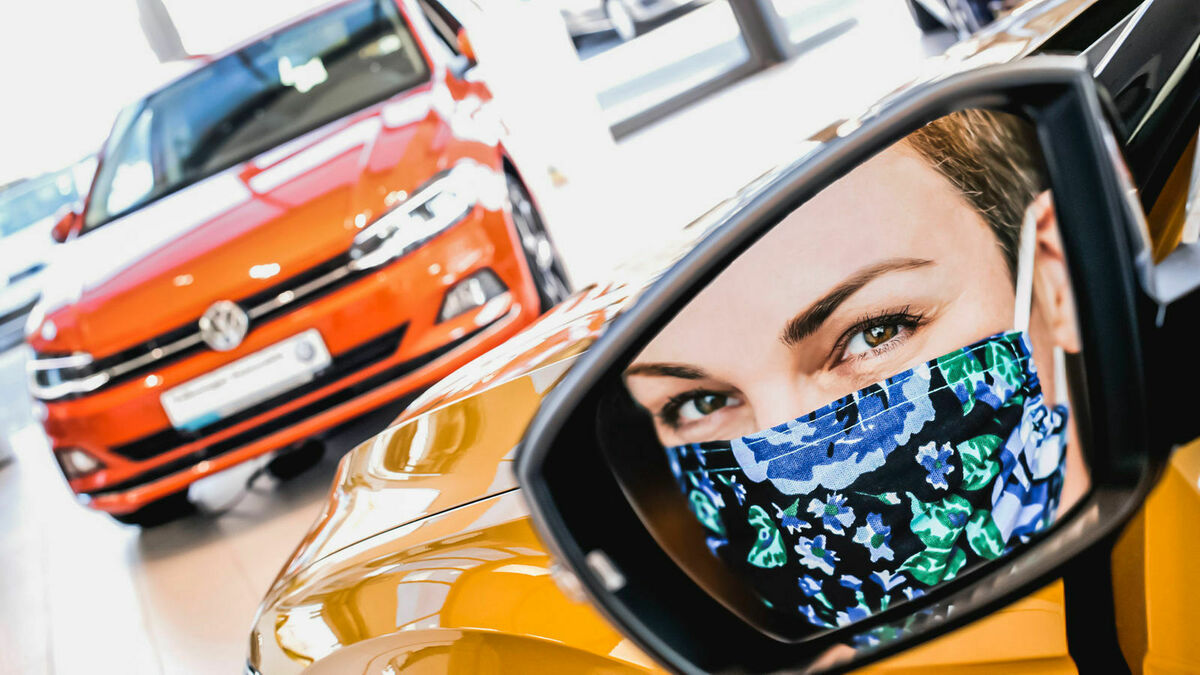 woman with mask in car mirror
