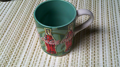 A 1998 Coca-Cola Coffee Cups/Mug with Handle from the Gibson Company green/red